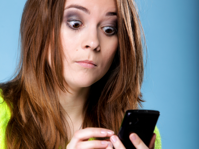 Surprised woman looking at phone